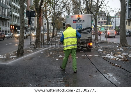 MILAN, ITALY-DECEMBER 02, 2014: worker water cleaning after a street market, in Milan.