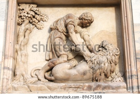 Milan, Italy. Famous landmark - the cathedral made of Candoglia marble. Samson slaying the lion - biblical story. - stock photo
