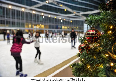 MILAN, ITALY - FEBRUARY 07: Christmas tree decorations with the ice skating rink in the background in Milan February 07, 2009. - stock photo