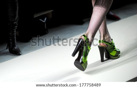 MILAN, ITALY-FEBRUARY 27, 2010: Close up of a model's green shoes on runway catwalk during the fall-winter fashion collection of Bottega Veneta. - stock photo