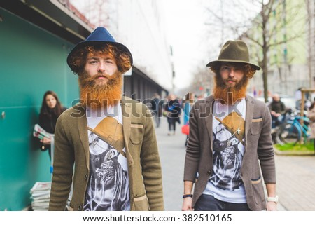 MILAN, ITALY - FEBRUARY 26, 2016: Couple of fashionable reddish bearded twins attending models and vips in the streets during Milan Fashion Week Women Fall/Winter 2015/2016