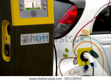 MILAN, ITALY-FEBRUARY, 23, 2012: Electric car recharging the battery on a car sharing dedicated parking spot, in downtown Milan.