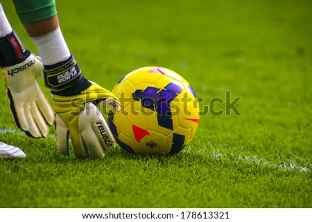 MILAN, ITALY-FEBRUARY 23, 2014: Goalkeeper gloves and yellow soccer ball on the green pitch of the San Siro stadium, during an italian Serie A soccer match. - stock photo