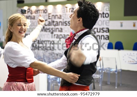 MILAN, ITALY - FEBRUARY 17: Performers dance in a traditional sicilian outfit at BIT International Tourism Exchange on february 17, 2012 in Milan, Italy. - stock photo