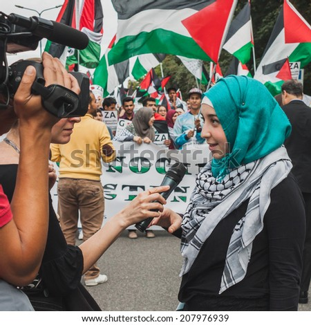 MILAN, ITALY - JULY 26: Young muslim woman talks to tv journalist while protesting against Gaza strip bombing in solidarity with Palestinians on JULY 26, 2014 in Milan. - stock photo