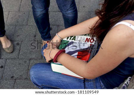 MILAN, ITALY-JUNE 20, 2012: College student's girl holding the Italian dictionary, before entering at school for the secondary school's final exams, at the Artemisia Gentileschi School in Milan. - stock photo