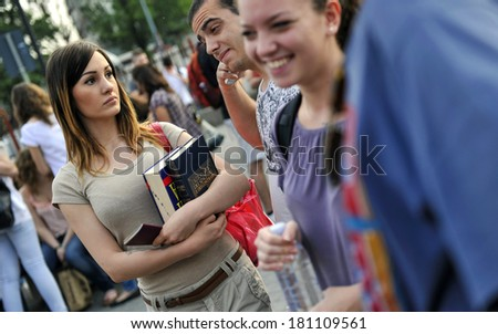 MILAN, ITALY-JUNE 20, 2012: College student's girls holding the Italian dictionary, before entering at school for the secondary school's final exams, at the Artemisia Gentileschi School in Milan. - stock photo