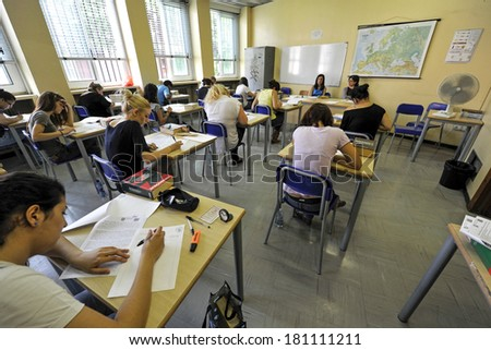 MILAN, ITALY-JUNE 20, 2012: College students seat on school desk in the exam room, for the secondary school's final exams, at the Artemisia Gentileschi School in Milan.
