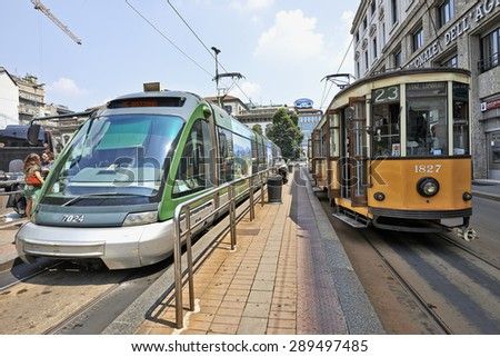 MILAN, ITALY- JUNE 11, 2015: Milan Orange Cable Car and Modern Street car ready for departure on subway platform in Milan, Italy . Symbol of mobility, ecology and alternative energy - stock photo