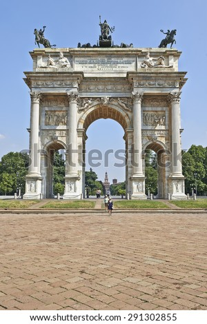 MILAN, ITALY- JUNE 11, 2015: Some tourist at the Parco Sempione, the Arch of Peace (Porta Sempione) and the Scorfesco palace in background, Milan, Italy. - stock photo