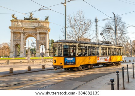 MILAN, ITALY- March 1st, 2016: Some tourist at the Parco Sempione, the Arch of Peace (Porta Sempione) and the Scorfesco palace in background, Milan, Italy. Typical old style Milanese tram.  - stock photo