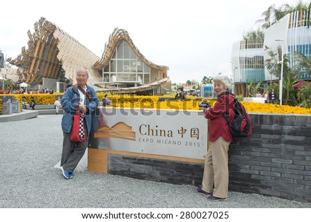MILAN, ITALY-MAY 04, 2015: chinese visitors posing for a picture at the entrance of the traditional building architecture of the China pavillion at the EXPO 2015, in Milan. - stock photo