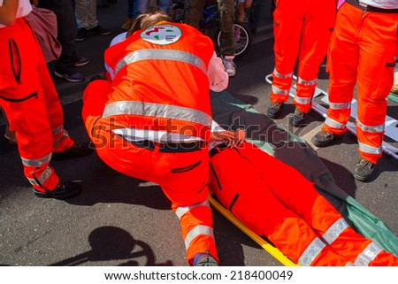 MILAN, ITALY - MAY, 18: Emergency personnel render aid to a girl during an emergency simulation on May 18, 2014 - stock photo