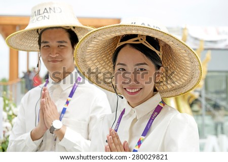 MILAN, ITALY-MAY 04, 2015: Thailand stewards wearing traditional hat receive visitors at the Thailand pavillion of the EXPO 2015, in Milan. - stock photo