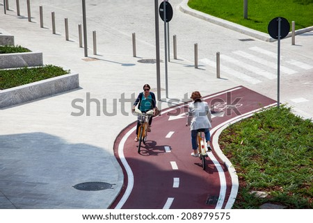 MILAN, ITALY - MAY 27: Two cyclists on a new bike path on May 27, 2014 - stock photo