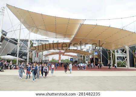 MILAN, ITALY-MAY 04, 2015: Visitors walk through EXPO 2015 pavillions on the main path, with architectural design rooftop, in Milan.  - stock photo