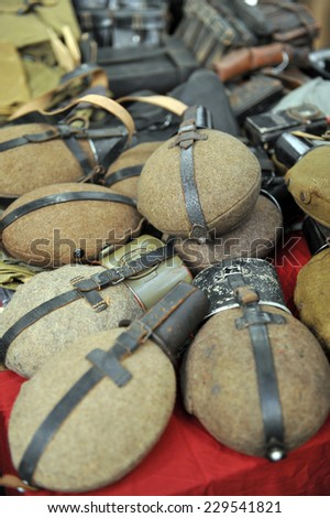 MILAN, ITALY - NOV 1: Bottles, Exhibitor sitting in his stand at Militalia, exhibition dedicated to militaria collectors and military associations on November 1, 2014 in Milan. - stock photo