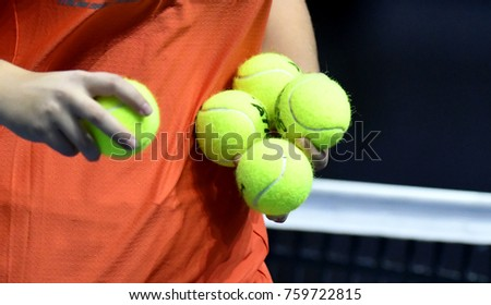 MILAN, ITALY-NOVEMBER 07, 2017: ball retriver's hands close up holding tennis balls, during the Next Gen ATP tennis tournament, in Milan.