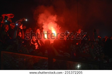 MILAN, ITALY-NOVEMBER 16, 2014: croatian fans light a smoke bomb during the international soccer match Italy vs Croatia, in Milan. - stock photo