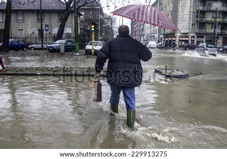 MILAN, ITALY-NOVEMBER 26, 2002: man crossing a flooded road during a flood caused by heavy rain, in Milan.