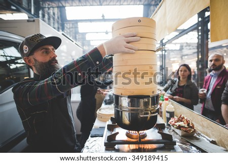 MILAN, ITALY - NOVEMBER 7: People visiting Eat Market, a street food parade with international dishes  in Milan on November, 7 2015. Chef cooking steamed ravioli