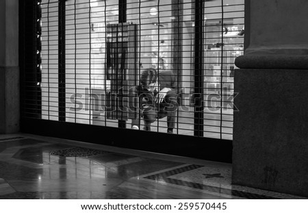 MILAN, ITALY - NOVEMBER, 24: Salesman close shop shutter on November 24, 2014 - stock photo