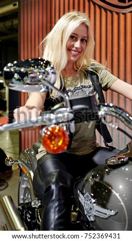 MILAN, ITALY-NOVEMBER 08, 2017: young model girl smiles riding a new model of Harley Davidson motorcycle, at EICMA, the international bike and motobike fair, in Milan.
