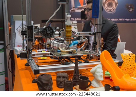MILAN, ITALY - OCTOBER 22: 3d printer printing chocolate cup at Smau, international exhibition of information communications technology on OCTOBER 22, 2014 in Milan. - stock photo