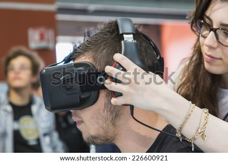 MILAN, ITALY - OCTOBER 24: Guy tries Oculus headset at Games Week 2014, event dedicated to video games and electronic entertainment on OCTOBER 24, 2014 in Milan. - stock photo