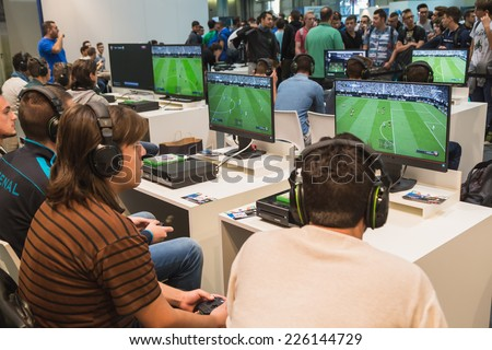 MILAN, ITALY - OCTOBER 24: Guys play at Games Week 2014, event dedicated to video games and electronic entertainment on OCTOBER 24, 2014 in Milan. - stock photo