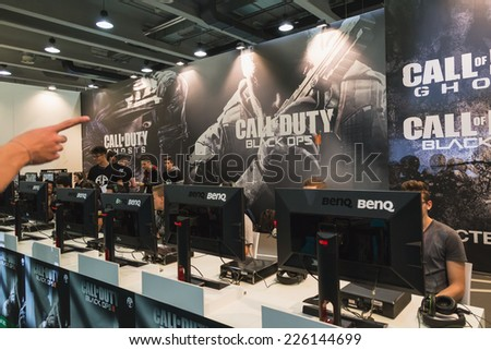 MILAN, ITALY - OCTOBER 24: People play at Games Week 2014, event dedicated to video games and electronic entertainment on OCTOBER 24, 2014 in Milan. - stock photo