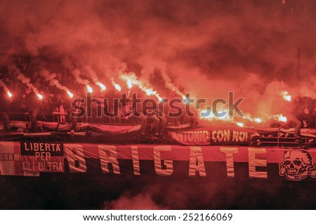 MILAN, ITALY-OCTOBER 11, 2005:  red smoke firecrackers at the san siro soccer stadium, during the derby match AC Milan vs FC Internazionale,in Milan. - stock photo