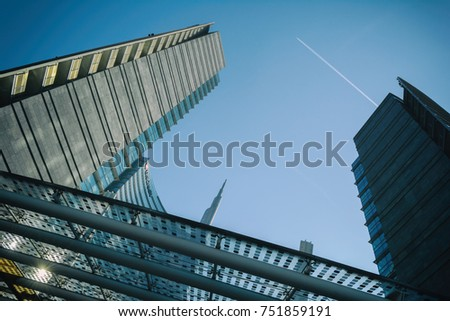 MILAN, ITALY - OCTOBER 9, 2017: View of the Unicredit skyscraper tower complex in front of the sky with an airplane trace, Piazza Gae Aulenti in the business district of Porta Garibaldi, cool toned