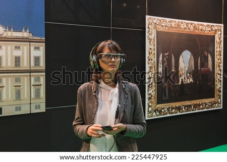 MILAN, ITALY - OCTOBER 22: Woman wearing glasses for augmented reality at Smau, international exhibition of information communications technology on OCTOBER 22, 2014 in Milan. - stock photo