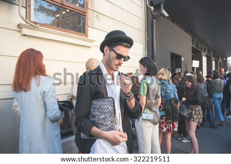 MILAN, ITALY - SEPTEMBER 25: People during Milan Fashion week, Italy on SEPTEMBER 25, 2015. Eccentric and fashionable man waiting models and vips outside city at Milan fashion week smoking cigarette - stock photo