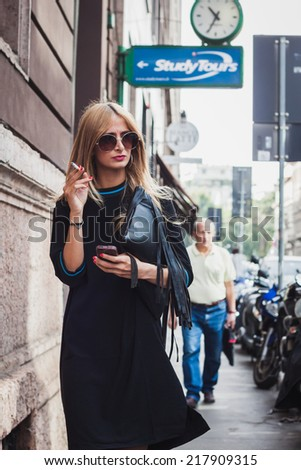 MILAN, ITALY - SEPTEMBER 17: Woman poses outside Byblos fashion shows building for Milan Women's Fashion Week on SEPTEMBER 17, 2014 in Milan.