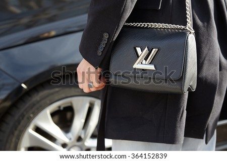 MILAN - JANUARY 18: Woman with Louis Vuitton twist lock black bag before Emporio Armani fashion show on January 18, 2015 in Milan, Italy. Man fashion fall winter 2016 / 2017 - stock photo
