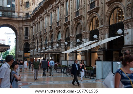 MILAN - JULY 3: Shoppers at the Galleria Vittorio Emanuele II on July 3, 2012 in Milan, Italy. Galleria Vittorio Emanuele II is considered as a direct progenitor of the modern day shopping mall. - stock photo