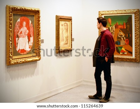 MILAN - MARCH 27: A man looks at paintings galleries during MiArt ArtNow, international exhibition of modern and contemporary art March 27, 2010 in Milan, Italy. - stock photo