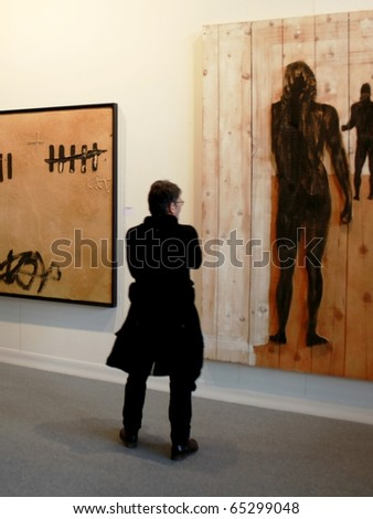 MILAN - MARCH 27: A woman look paintings galleries at MiArt ArtNow, international exhibition of modern and contemporary art March 27, 2010 in Milan, Italy. - stock photo