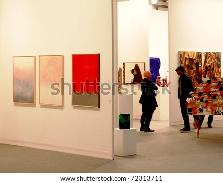 MILAN - MARCH 27: People walk through works of art galleries during MiArt ArtNow, international exhibition of modern and contemporary art March 27, 2010 in Milan, Italy. - stock photo