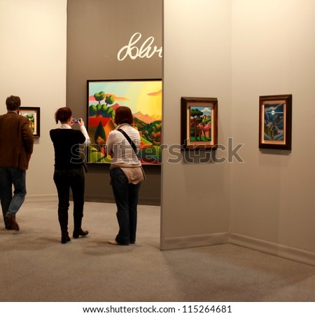 MILAN - MARCH 27: Women look at paintings galleries during MiArt ArtNow, international exhibition of modern and contemporary art March 27, 2010 in Milan, Italy. - stock photo