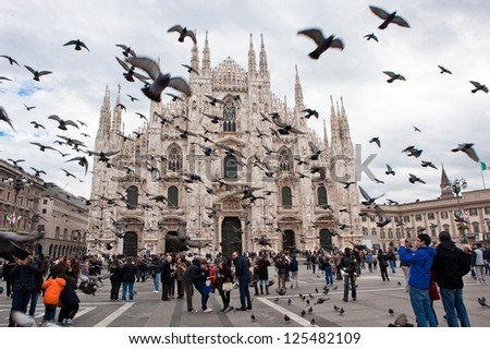 MILAN - NOV 3: Tourists visit the largest cathedral in Italy, Duomo di Milano while a flock of pigeons flies overhead surprisingly on Nov 3, 2012 in Milan.The Cathedral is a main landmark of the city. - stock photo