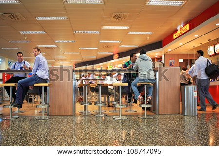 MILAN - SEP 21: People sitting in restaurant at Malpensa International Airport - largest airport in northern Italy serves international and domestic flights in Milan, Italy on September 21, 2010. - stock photo
