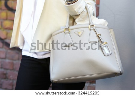 MILAN - SEPTEMBER 24: Woman poses for photographers before Fendi show with cream color Prada bag during Milan Fashion Week Day 2, Spring / Summer 2016 street style on September 24, 2015 in Milan. - stock photo