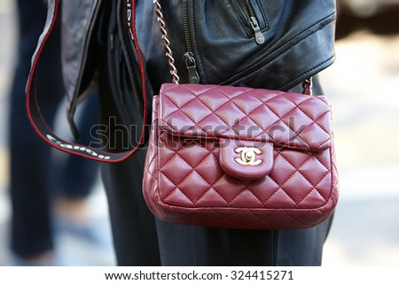 MILAN - SEPTEMBER 24: Woman poses for photographers before Fendi show with red Chanel bag during Milan Fashion Week Day 2, Spring / Summer 2016 street style on September 24, 2015 in Milan. - stock photo