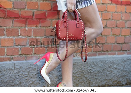 MILAN - SEPTEMBER 24: Woman poses for photographers before Fendi show with Valentino red bag during Milan Fashion Week Day 2, Spring / Summer 2016 street style on September 24, 2015 in Milan. - stock photo