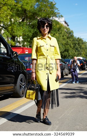MILAN - SEPTEMBER 24: Woman poses for photographers with yellow trench before Fendi show during Milan Fashion Week Day 2, Spring / Summer 2016 street style on September 24, 2015 in Milan.