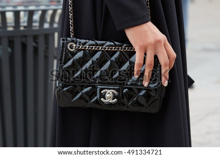 MILAN - SEPTEMBER 22: Woman with black Chanel patent leather bag before Genny fashion show, Milan Fashion Week street style on September 22, 2016 in Milan.