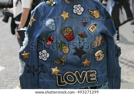 MILAN - SEPTEMBER 23: Woman with blue jeans jacket with Love writing before Giamba fashion show, Milan Fashion Week street style on September 23, 2016 in Milan.